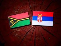 Vanuatu flag with Serbian flag on a tree stump isolated. Vanuatu flag with Serbian flag on a tree stump royalty free stock photo