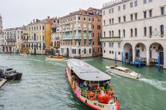 Vaparetto water bus, water taxis/ taxicabs and other boats sailing between buildings in the Grand Canal, Venice stock photos