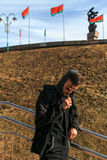 Vape人 太阳镜的一个英俊的年轻白人沿着走台阶并且抽一根电子香烟 图库摄影