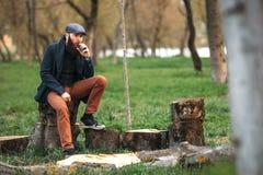 Vape人 有休息在剁木柴以后和vaping一根电子香烟的一个残酷有胡子的年轻人的照片在村庄 库存照片