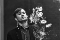 Vape人 年轻英俊的白人让圆环在从电子香烟的蒸汽外面 北京,中国黑白照片 免版税库存图片