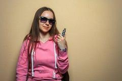 Vape女孩 年轻逗人喜爱的妇女画象桃红色有冠乌鸦和太阳镜的在她的手上的拿着一根电子香烟在赭色对面 免版税图库摄影