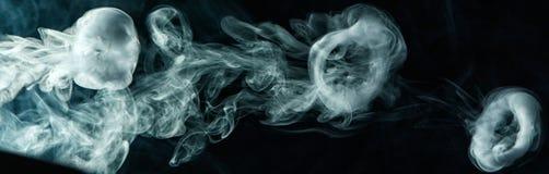 Vape把戏在黑暗的背景的烟圆环 库存照片