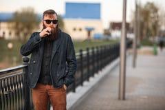 Vape有胡子的人在真正的生活中 年轻人画象有大胡子的在vaping一根电子香烟的太阳镜 免版税库存图片
