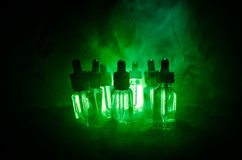 Vape概念 烟云和vape液体瓶在黑暗的背景 影响巨大轻的当事人性能 有用当背景或vape广告 图库摄影