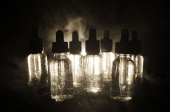 Vape概念 烟云和vape液体瓶在黑暗的背景 影响巨大轻的当事人性能 有用当背景或vape广告 免版税库存照片