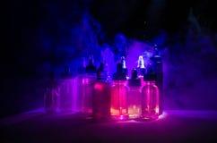Vape概念 烟云和vape液体瓶在黑暗的背景 影响巨大轻的当事人性能 库存照片