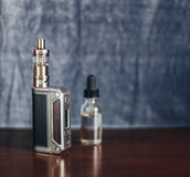 Vape设备、E香烟vaping的,液体在瓶和手机在s 库存照片