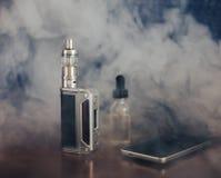 Vape设备、E香烟vaping的,液体在瓶和手机 免版税库存图片