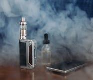 Vape设备、E香烟vaping的,液体在瓶和手机 图库摄影
