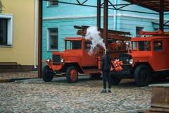 Vape 一个年轻英俊的人是常设近的老消防车和让从一根电子香烟的蒸汽 免版税库存图片