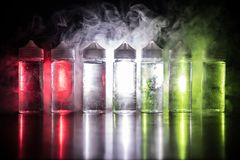 Vape concept. Smoke clouds and vape liquid bottles on dark background. Light effects. Selective focus stock photos