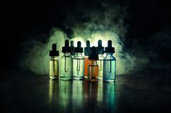 Vape concept. Smoke clouds and vape liquid bottles on dark background. Light effects. Useful as background or vape advertisement o. R vape background Stock Photo