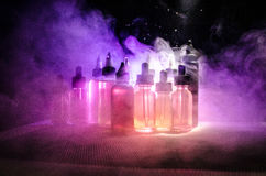 Vape concept. Smoke clouds and vape liquid bottles on dark background. Light effects. Useful as background or vape advertisement or vape background Stock Photos