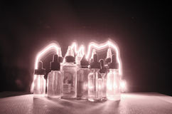 Vape concept. Smoke clouds and vape liquid bottles on dark background. Light effects. Useful as background or vape advertisement or vape background Stock Photography