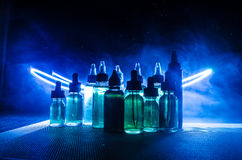 Vape concept. Smoke clouds and vape liquid bottles on dark background. Light effects. Stock Images