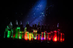 Vape concept. Smoke clouds and vape liquid bottles on dark background. Light effects. Useful as background or vape advertisement or vape background royalty free stock photography