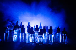 Vape concept. Smoke clouds and vape liquid bottles on dark background. Light effects. Stock Photography