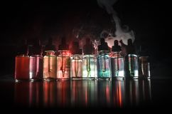 Vape concept. Smoke clouds and vape liquid bottles on dark background. Light effects. Useful as background or vape advertisement o. R vape background Royalty Free Stock Images