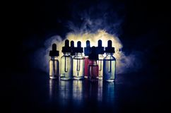 Vape concept. Smoke clouds and vape liquid bottles on dark background. Light effects. Useful as background or vape advertisement o. R vape background Stock Image