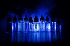 Vape concept. Smoke clouds and vape liquid bottles on dark background. Light effects. Useful as background or vape advertisement o. R vape background Royalty Free Stock Photography