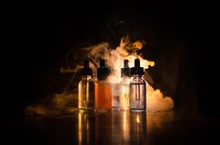 Vape concept. Smoke clouds and vape liquid bottles on dark background. Light effects. Useful as background or vape advertisement o. R vape background Royalty Free Stock Photo