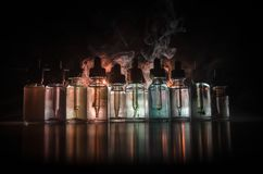 Vape concept. Smoke clouds and vape liquid bottles on dark background. Light effects. Useful as background or vape advertisement o. R vape background stock photography