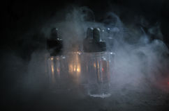 Vape concept. Smoke clouds and vape liquid bottles on dark background. Light effects. Useful as background or vape advertisement. Royalty Free Stock Photos