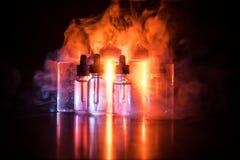 Vape concept. Smoke clouds and vape liquid bottles on dark background. Light effects. Selective focus stock image