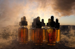 Vape concept. Smoke clouds and vape liquid bottles at sunset time. Blured background. Light effects. Useful as background or vape Stock Photos