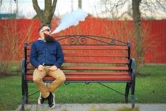 Vape De jonge brutale mens met grote baard en modieus kapsel in zonnebril rookt een elektronische sigaret op de rode bank stock fotografie