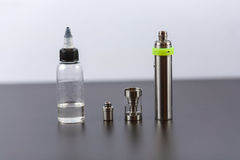 Vape Delar av e-cigaretten och en krus med vätska för personliga vaporisers Elektroniskt cigarettslut upp royaltyfri fotografi