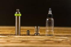 Vape Delar av e-cigaretten och en krus med vätska för personliga vaporisers Elektroniskt cigarettslut upp royaltyfri bild