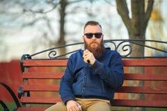 Vape Den unga brutala mannen med stor skägg- och innegrejfrisyr i solglasögon röker en elektronisk cigarett på den röda bänken royaltyfria bilder