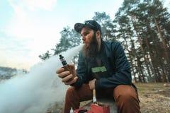 Vape Den unga mannen med det stora skägget i ett lock röker en elektronisk cigarett i skogen arkivbild