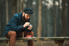 Vape Den unga mannen med det stora skägget i ett lock stuvar bomull in i en elektronisk cigarett arkivfoto