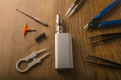 Vape device or electronic cigarette with vaping tools and access. Tools for vaping device, electronic cigarette, e-cigarette, box mod, accessories isolated over royalty free stock image