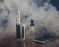 Vape devices, E-cigarette for vaping, liquid in the bottle and mobile phone. At smoke on wooden table royalty free stock image
