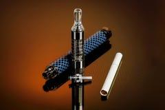 Vape, elektronische Zigarette explodierte nahe bei einer herkömmlichen Zigarette auf einem dunklen Hintergrund Lizenzfreies Stockbild