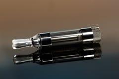 Vape, elektronische Zigarette explodierte nahe bei einer herkömmlichen Zigarette auf einem dunklen Hintergrund Lizenzfreie Stockbilder