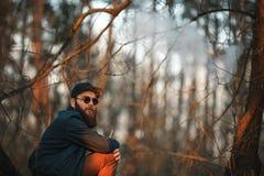 Vape En brutal ung man med ett enormt skägg i solglasögon och ett lock röker en elektronisk cigarett i träna på solnedgången arkivfoton