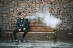 Vape En ung stilig grabb sitter på bänken, och slag ångar från en elektronisk cigarett arkivfoton