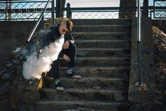 Vape En ung stilig grabb sitter på trappan, och slag ångar från en elektronisk cigarett royaltyfri bild