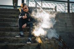 Vape En ung stilig grabb sitter på trappan, och slag ångar från en elektronisk cigarett arkivfoton