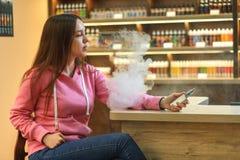Vape-Frau Junges nettes Mädchen im rosa Hoodie, der eine elektronische Zigarette raucht stockbild