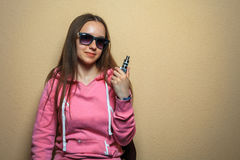 Vape girl. Portrait of young cute woman in pink hoodie and sunglasses holding an electronic cigarette in her hand opposite sienna. Background. Model royalty free stock photography