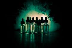 Vape-Konzept Rauchwolken und vape flüssige Flaschen auf dunklem Hintergrund Große Party und Leistung Nützlich als Hintergrund- od Lizenzfreie Stockbilder