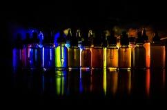 Vape-Konzept Rauchwolken und vape flüssige Flaschen auf dunklem Hintergrund Große Party und Leistung Nützlich als Hintergrund- od Lizenzfreies Stockfoto