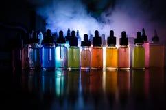 Vape-Konzept Rauchwolken und vape flüssige Flaschen auf dunklem Hintergrund Große Party und Leistung Nützlich als Hintergrund- od Stockfotos