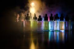 Vape-Konzept Rauchwolken und vape flüssige Flaschen auf dunklem Hintergrund Große Party und Leistung Nützlich als Hintergrund- od Stockbild